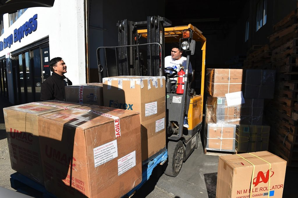Emil Gopilan of Vancouver's Manila Cargo Express unloads a customer's order in the warehouse.